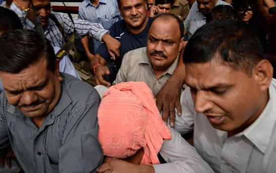 Indian policemen escort the juvenile (C, in pink hood), accused in the December 2012 gang-rape of a student, to a court in New Delhi on August 31, 2013.
