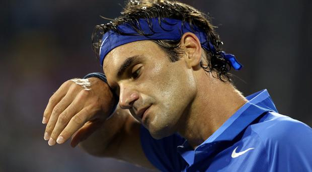 Roger Federer looks on during his fourth round defeat to Tommy Robredo of Spain