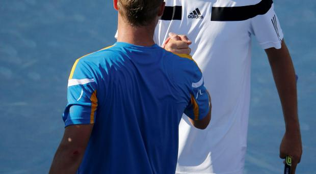Mikhail Youzhny of Russia (R) is congratulated by Lleyton Hewitt of Australia after their match