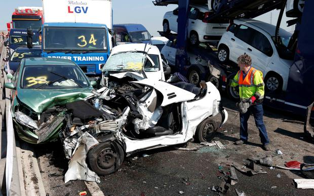 A rescue worker stands amongst the wreckage of some of the 100 vehicles involved in multiple collisions, which took place in dense fog during the morning rush hour, on the Sheppey Bridge in Kent, east of London, September 5, 2013.
