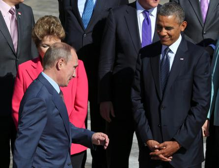 Russian President Vladimir Putin walks past US President Barack Obama as they arrive for the family picture event during the G20 summit in St.Petersburg