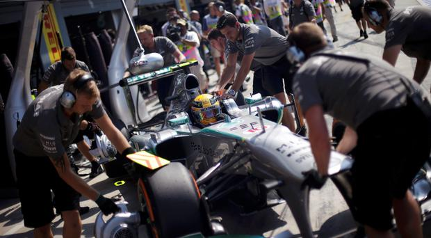 Mercedes Formula One mechanics push the car of Lewis Hamilton of Britain during the second practice session of the Italian F1 Grand Prix at the Monza circuit
