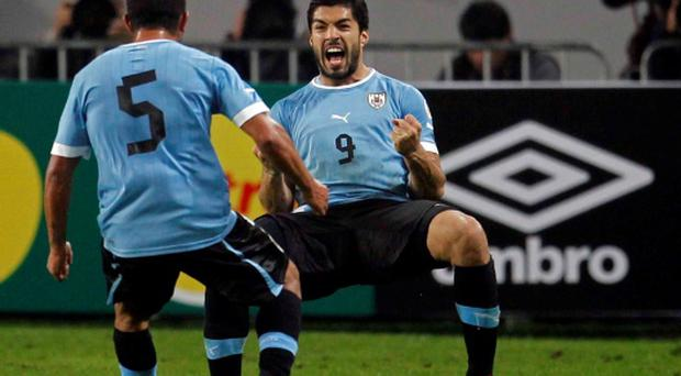 Uruguay's Luis Suarez (facing camera) celebrates with team-mate Walter Gargano after scoring his second goal against Peru