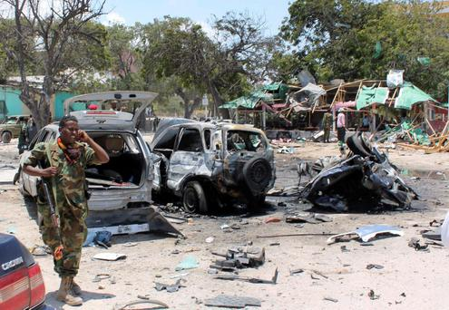 A Somali soldier walks past destroyed vehicles at the scene of a suicide car bombing near a restaurant in Hamaerweyne district in Mogadishu