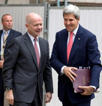 Britain's Foreign Secretary William Hague (L) greets U.S. Secretary of State John Kerry