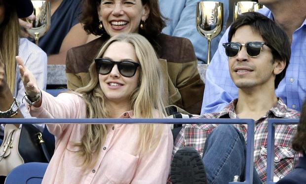 Amanda Seyfried, left, and Justin Long, right, watch play between Rafael Nadal, of Spain, and Novak Djokovic, of Serbia, during the men's singles final of the 2013 U.S. Open tennis tournament