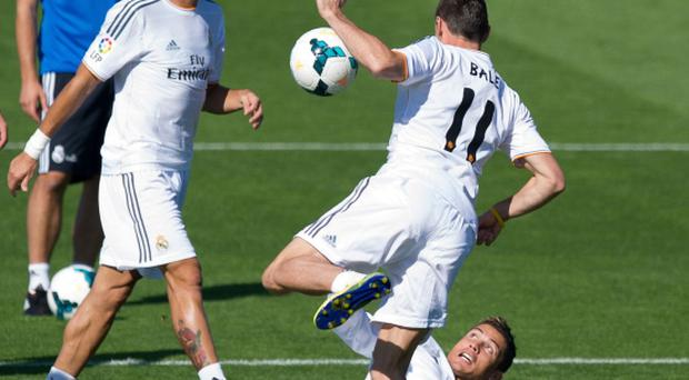 Real Madrid's new signing Gareth Bale is tackled by Cristiano Ronaldo while teammate Pepe looks on during a team training session on September today