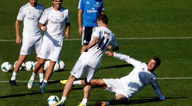 Real Madrid's Gareth Bale (C) is tackled by Cristiano Ronaldo (R) as Karim Benzema (L) and Pepe look on during their training session at Valdebebas sports grounds in Madrid