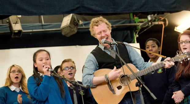 13/09/2013. Pictured is Oscar winner and renowned musician Glen Hansard performing 'Falling Slowly' with the choir at St Tiernan's Community School, Dundrum raising the school's first Green Flag from An Taisce. Photo: El Keegan