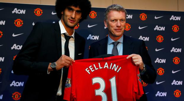 Manchester United's Marouane Fellaini (L) poses with manager David Moyes after signing last September