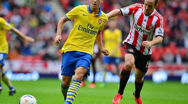 Arsenal's Mesut Ozil and Sunderland's David Vaughen (right) in action during the Barclays Premier League match at the Stadium of Light
