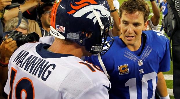 Denver Broncos quarterback Peyton Manning (L) talks with his brother, New York Giants quarterback Eli Manning after the Broncos defeated the Giants last night