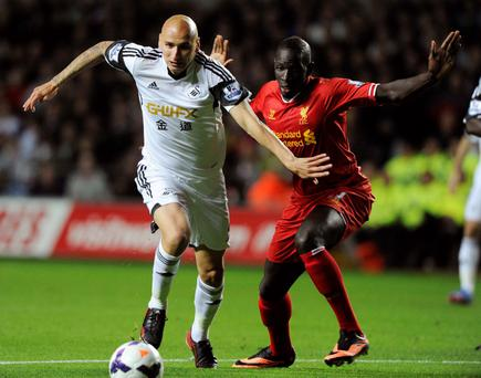 Swansea City's Jonjo Shelvey (L) passes Liverpool's Mamadou Sakho before scoring a goal during their Premier League soccer match at the Liberty Stadium, Swansea
