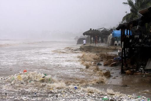 Waves flood a beach in Acapulco after Hurricane Ingrid and tropical depression Manuel brought heavy rains to Mexico's Gulf and Pacific coasts