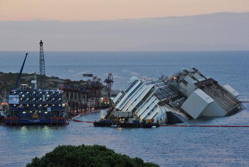 Engineers work on the wreckage of the Costa Concordia during the evening as the parbuckling operation to raise the ship continues
