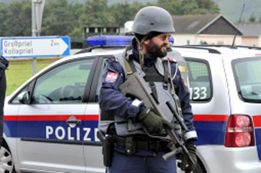 Police stand near the villages of Grosspriel and Kollapriel some 90km west of Vienna where a man is barricading himself inside a farm building.