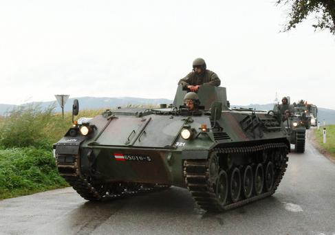 Austrian army armoured personnel carriers approach a crime scene near Melk west of Vienna