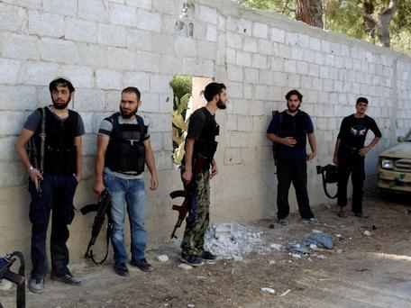 Free Syrian Army fighters carry weapons at the fifth bridge area on Damascus International Airport Road
