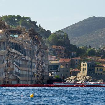ISOLA DEL GIGLIO, ITALY - SEPTEMBER 18: The previously submerged severely damaged right side of the Costa Concordia cruise ship is seen on September 18, 2013 in Isola del Giglio, Italy. The vessel, which sank on January 12, 2012, was successfully righted during a painstaking operation yesterday morning. The ship will eventually be towed away and scrapped. It was the first time the procedure, known as parbuckling, had been carried out on a vessel as large as Costa Concordia. (Photo by Marco Secchi/Getty Images)