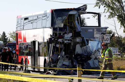 A firefighter walks in front of the scene of an accident involving a bus and a train in Ottawa