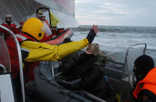 Russian Coast guard officer, center, pointing a knife at a Greenpeace International activist, left in yellow