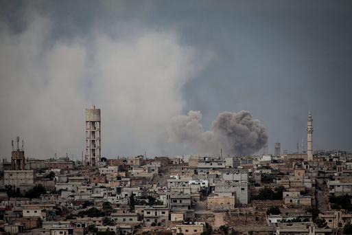 Smoke rises after a TNT bomb was thrown from a helicopter, hitting a rebel position during heavy fighting between troops loyal to president Bashar Assad and opposition fighters in Syria