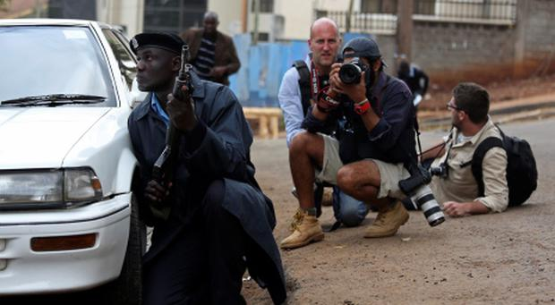 A policeman and photographers take cover after hearing gun shots near the Westgate shopping centre