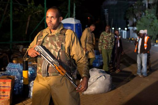 A police officer walks towards the edge of a security perimeter put into place a distance from the Westgate Shopping Centre in Nairobi, in the early hours of the morning during a standoff operation between Kenyan security forces and gunmen inside the building