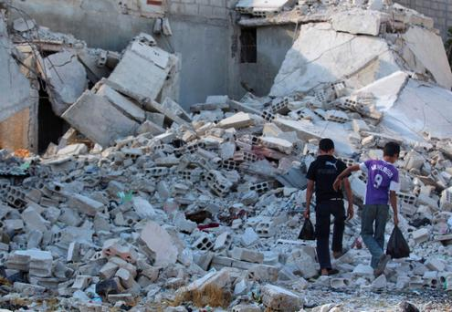 Boys walk amidst the rubble of damaged buildings in Duma neighbourhood of Damascus September 23, 2013.