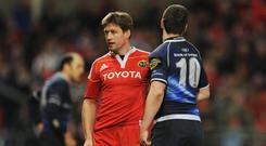 Ronan O'Gara, Munster, brushes off Jonathan Sexton, Leinster.