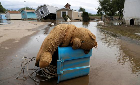 A stuffed teddy bear chair lies slumped over in the flooded Eastwood Village