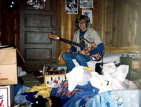 A young Kurt Cobain plays guitar in his childhood home