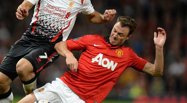 Liverpool's Luis Suarez (left) and Manchester United's Jonny Evans (right) battle for the ball during last night's game