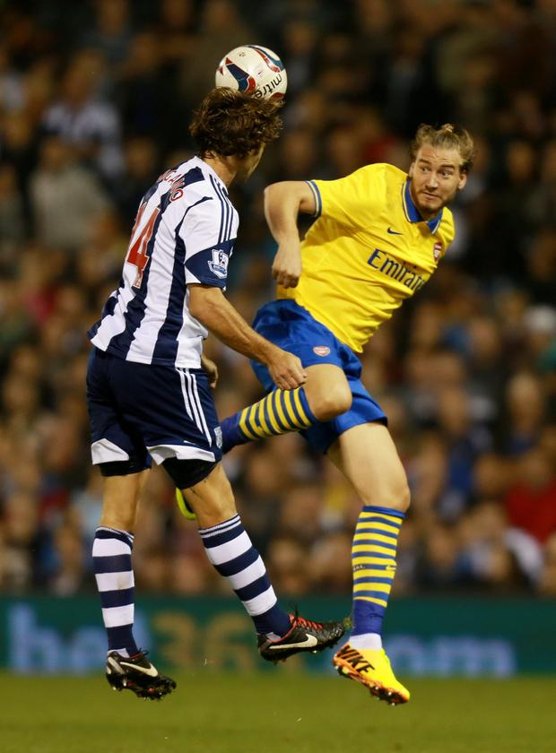 Arsenal's Nicklas Bendtner (right) challenges WBA's Diego Lugano during the Capital One Cup, Third round match at The Hawthorns last night