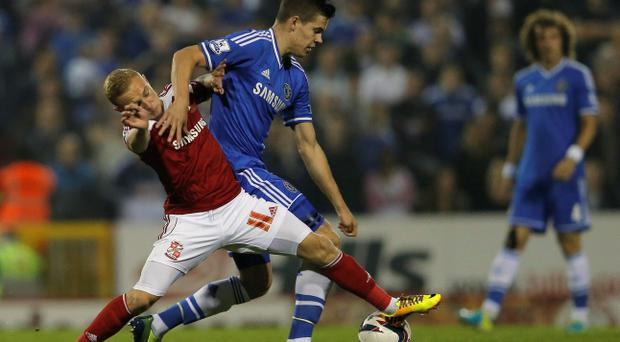 Swindon Town's Alex Pritchard (L) challenges Chelsea's Marko Van Ginkel. The Chelsea midfielder suffered his injury after this tackle