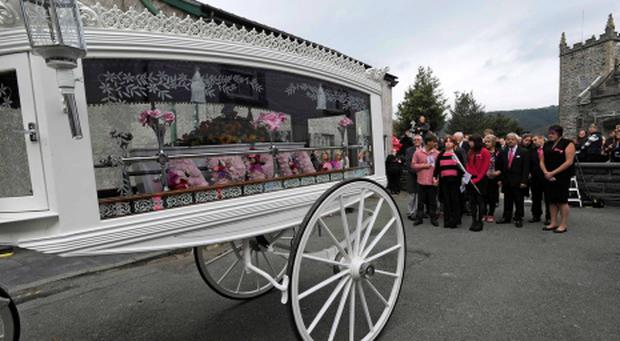 The coffin of April Jones is carried by a horse-drawn carriage following her funeral service at St Peter's Church in Machynlleth