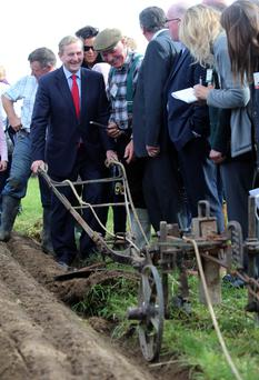 Taoiseach Enda Kenny shares a joke with ploughing competitor Gerry King at the National Ploughing championships in Ratheniska, Co Laois.