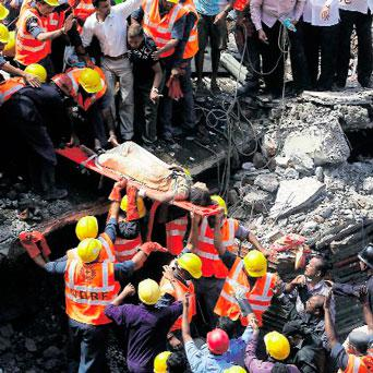 Rescue workers carry a woman from the rubble at the site of a collapsed residential building in Mumbai.