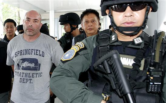 Alleged American drug trafficker Joseph Manuel Hunter (L) is escorted by Thai commandos as he arrives to board a chartered jet for extradition to the USA at Don Mueang airport in Bangkok