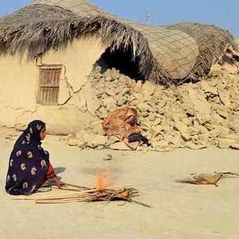 A survivor of an earthquake burns wooden sticks near the rubble of a mud house after it collapsed following an earthquake in the southwestern Pakistani province of Baluchistan