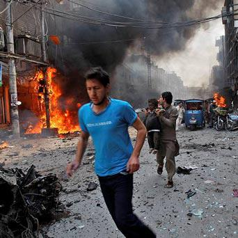 Pakistani run away from the site of a blast shortly after a car explosion in Peshawar, Pakistan,