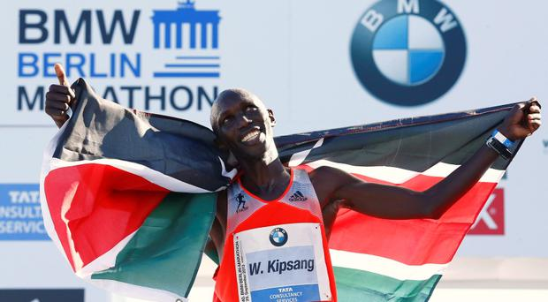 Wilson Kipsang of Kenya gestures as he celebrates with the Kenyan national flag after winning in the 40th Berlin marathon