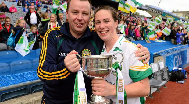 Offaly captain Siobhan Flannery celebrates with manager Eamonn Ryan and the West County Hotel cup after the game.