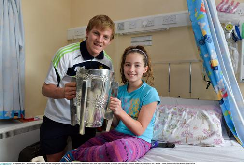 Clare's Padraic Collins with ten year old Aisling Keogh, from Raharney, Co. Westmeath, and the Liam MacCarthy cup on a visit by the All-Ireland Senior Hurling Champions to Our Lady's Hospital for Sick Children, Crumlin.