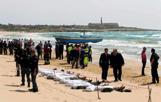 Rescue workers stand next to bodies of migrants who drowned on the beach in the Sicilian village of Sampieri