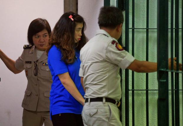 Noppawan Tangudomsuk (C) is detained by criminal court officers at the criminal court in Bangkok