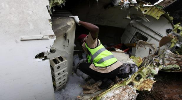 A rescue worker inspects the wreckage of a charter passenger jet which crashed soon after take off from Lagos airport, Nigeria, Thursday, Oct. 3, 2013. Officials said there were casualties but refused to confirm reports of several deaths. (AP Photo/Sunday Alamba)