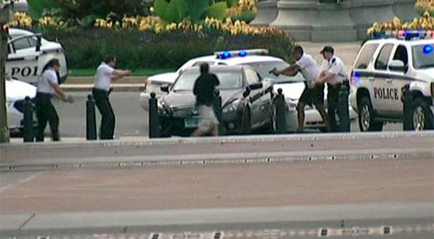 Police surround a car shortly before the incident