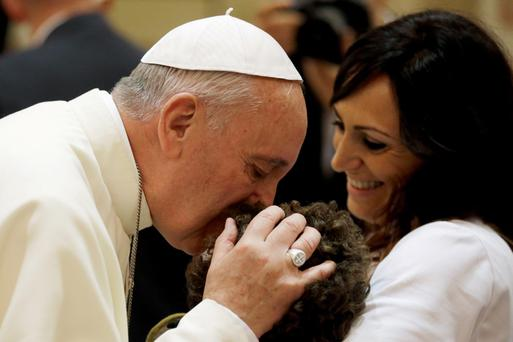 Pope Francis blesses a disabled person during his visit at the Serafico Institue in Assisi