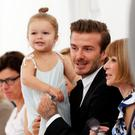 David Beckham holds his daughter Harper as he speaks to Vogue editor Anna Wintour while waiting for a presentation of the Victoria Beckham Spring/Summer 2014 collection during New York Fashion Week. REUTERS/Lucas Jackson